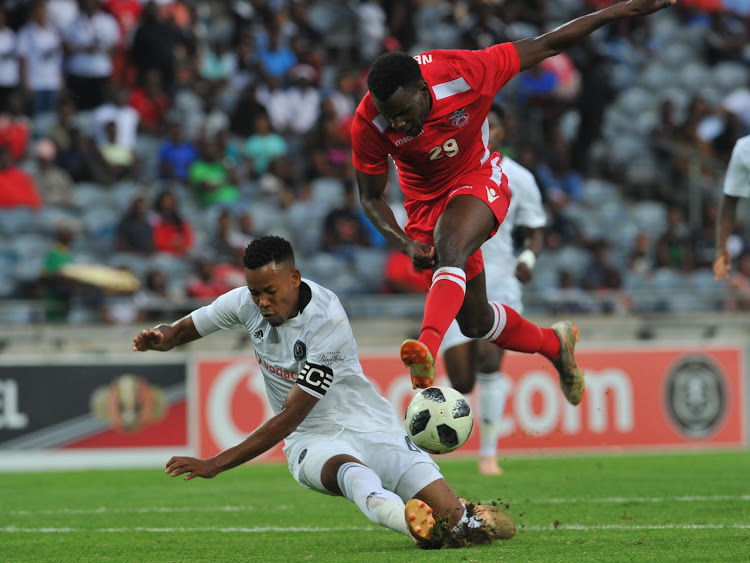 Orlando Pirates' centre-back and captain Happy Jele (L) makes a match-saving tackle to block Nekundi Panduleni of African Stars during the Caf Champions League match at Orlando Stadium in Orlando, Soweto, on December 15 2018.