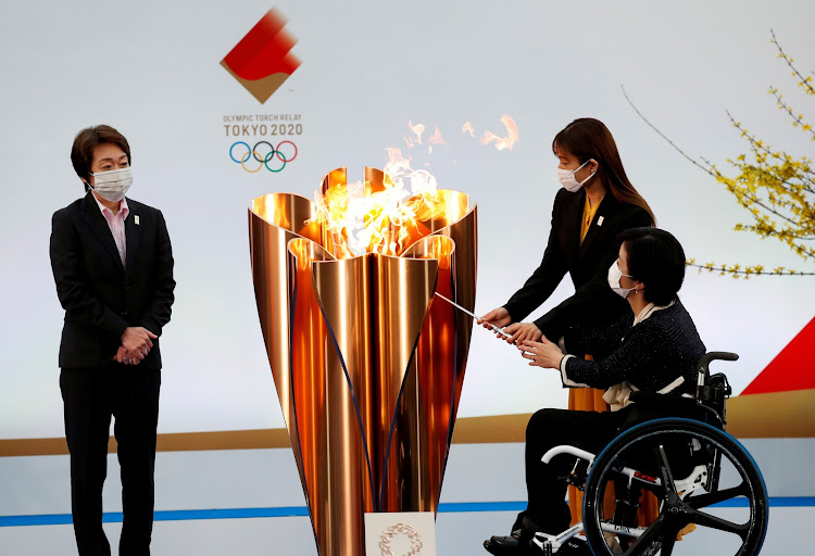 Tokyo 2020 President Seiko Hashimoto looks on as actor Satomi Ishihara and Paralympian Aki Taguchi light the celebration cauldron on the first day of the Tokyo 2020 Olympic torch relay in Fukushima, Japan on March 25, 2021