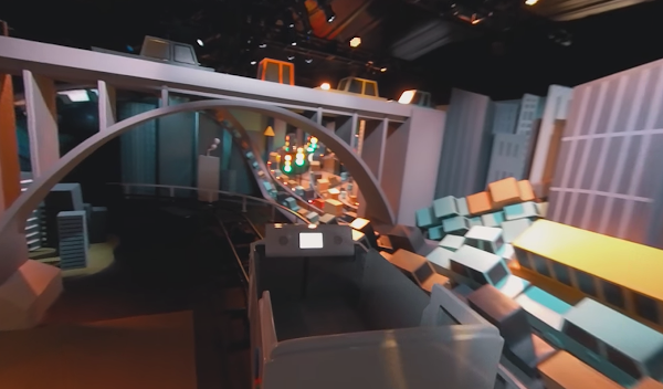 A rollercoaster car going underneath a small bridge through miniature cityscape set in a conference hall.