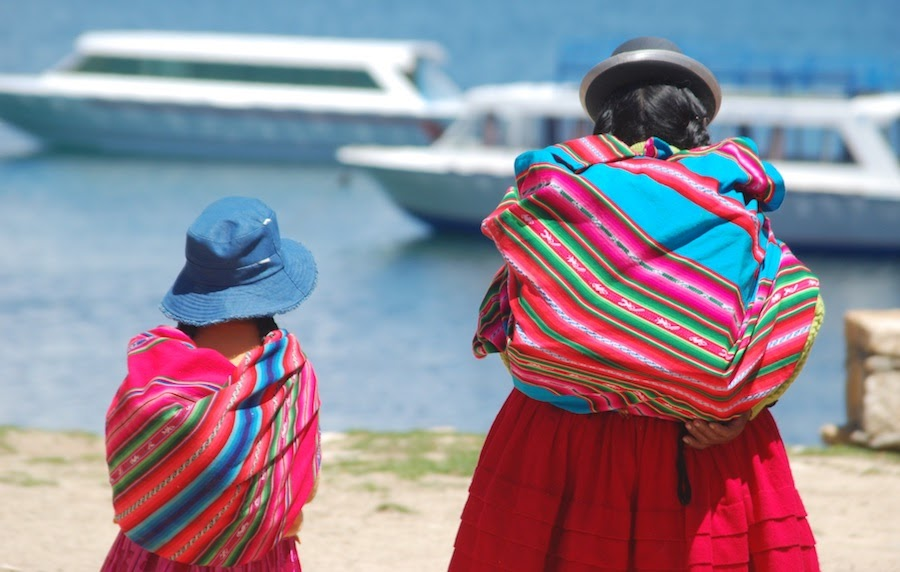 women and daughter cholitas walking towards ferries on the shore of el lago titicaca in copacabana bolivia latin america