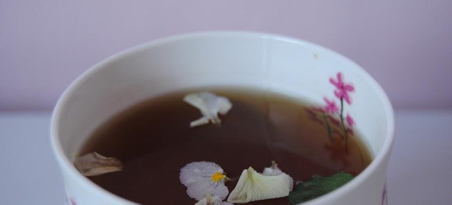 Napar ziołowy na włosy w białej filiżance na stole
