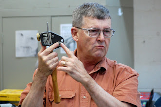 Photo: Ernie explained how grinding jigs worked and short cuts to setting them up.  Here he shows how he holds it so that he keeps his fingers off the grinder and in control of the tool.
