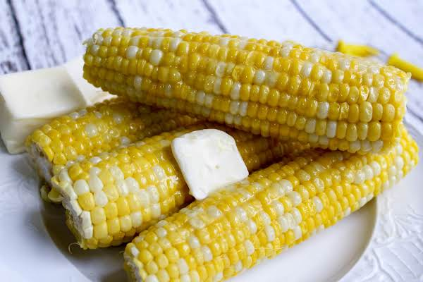 Ears Of Corn On A Plate With A Pat Of Butter.