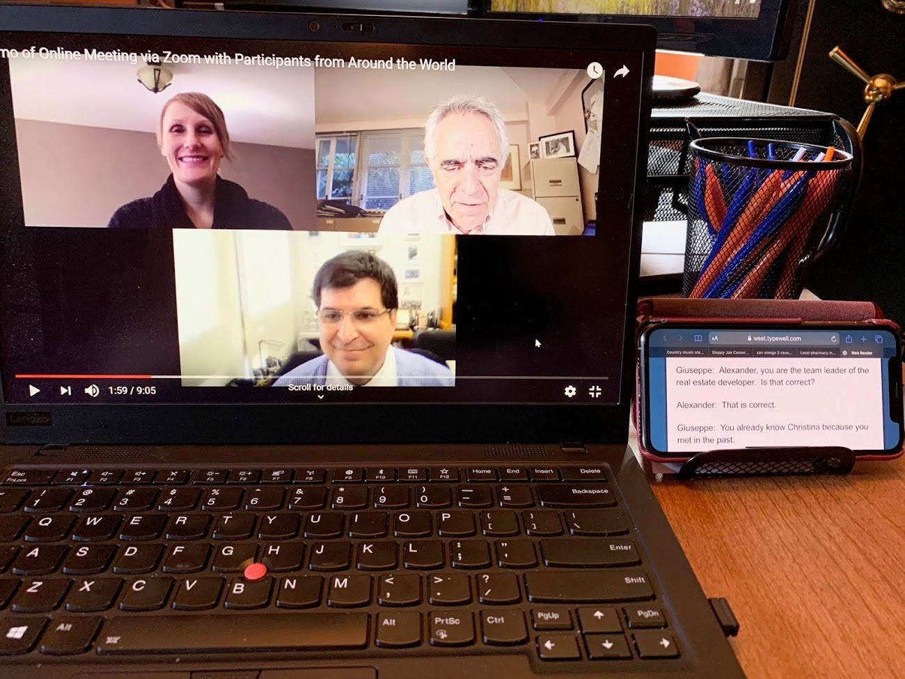 Zoom meeting on a laptop with a smartphone next to it displaying live transcript