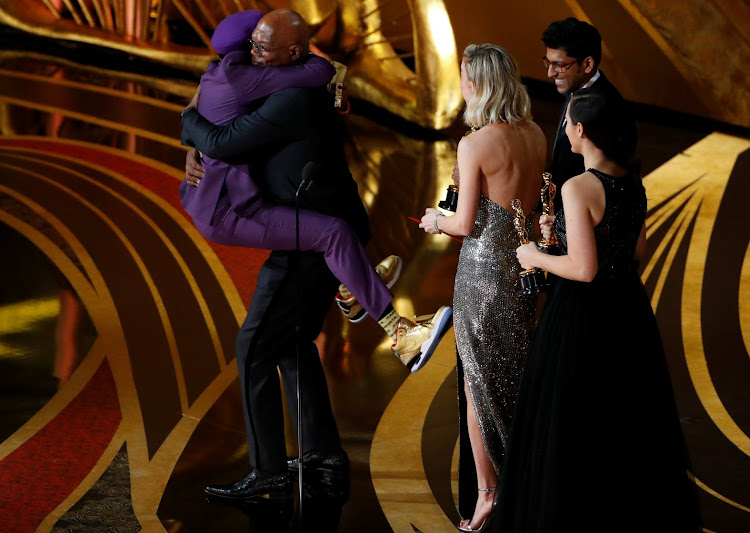 Spike Lee embraces Samuel L Jackson as he wins best adapted screenplay.
