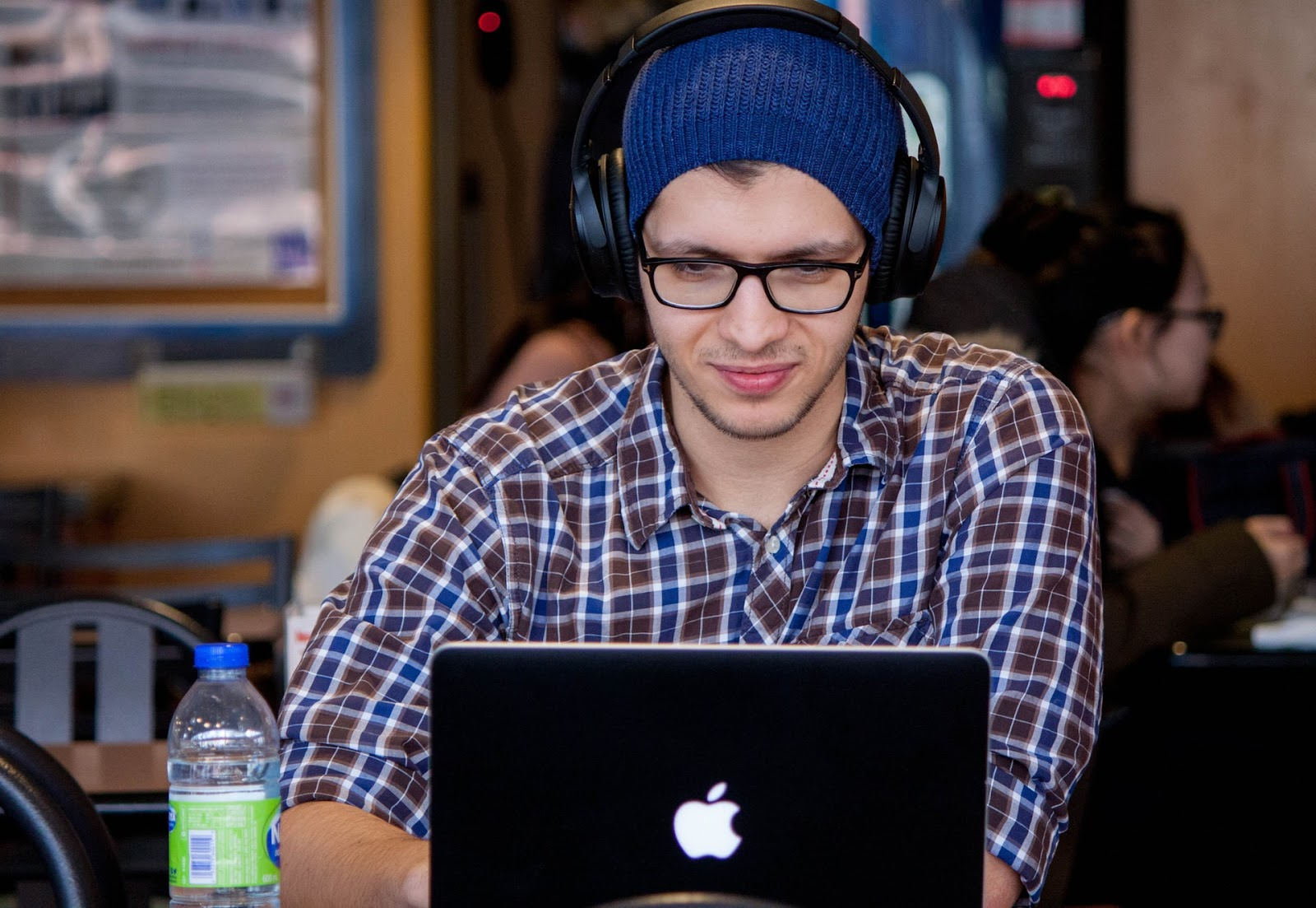 a man with black headphones on a computer in a cafeteria