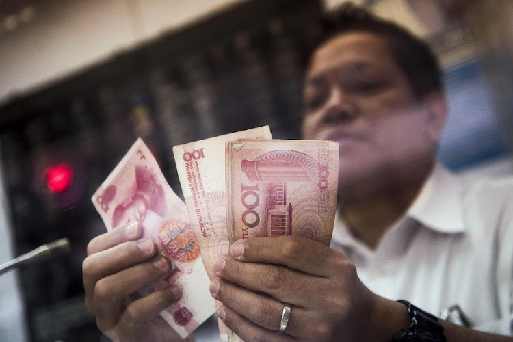 An employee at a currency exchange store counts bank notes in Hong Kong, China. File Picture: BLOOMBERG
