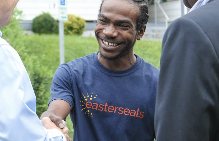 "A man wearing an ""Easterseals"" shirt shaking another man's hand"