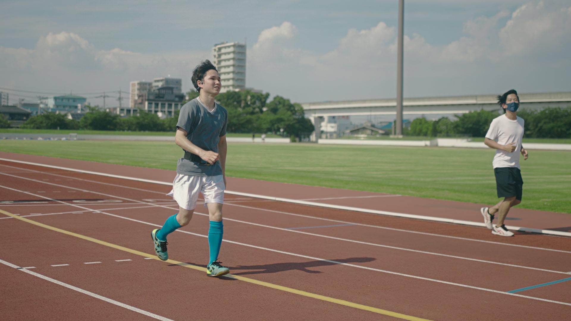 写真:コース上に貼られた黄色いガイドラインのテープに沿って軽やかに走るサッカーのユニフォームを着た男性のテスト走者と、それを見守るスタッフ。