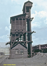 Photo: 077-40.  East side of coaling tower.  Tower was similar but not identical to one still at Chama.  Drop bottom gondolas on ramp at right are loaded with arriving coal.  7/28/60.