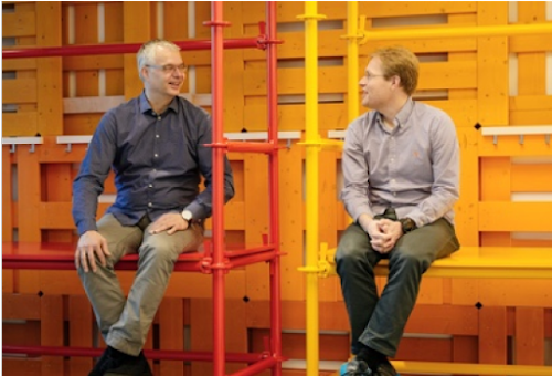 Two men talking, sitting on metal shelves.