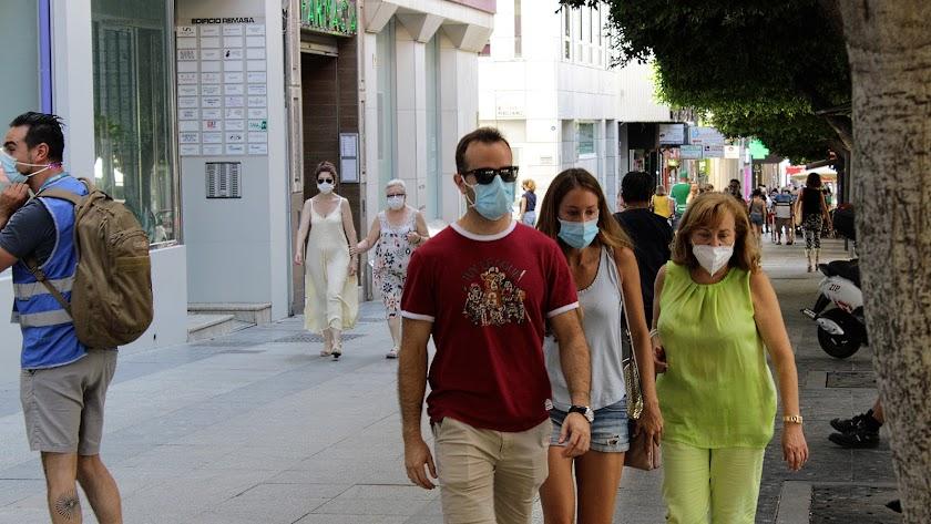Almerienses circulan por la calle con la mascarilla obligatoria.