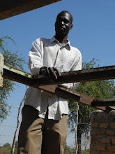 Photo: View of Mou standing at the locally-welded frame where the solar panels will be mounted.