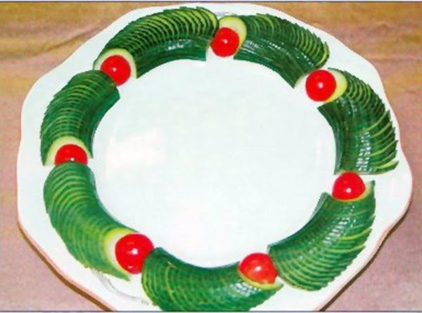 Decorate the edge of a plate with the cucumber 'fans' alternating them with cherry...