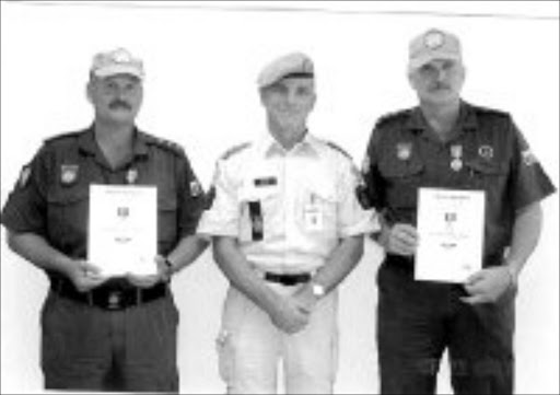 AWARDED: Tony Mundell, left, and Robbie Robertse, right, with UN police commissioner in Sudan Kai Vittrup when the two KwaZulu-Natal police officers were awarded medals of excellence. © Unknown.