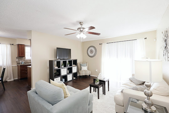 One bedroom model unit with spacious living room with wood-style flooring and a ceiling fan