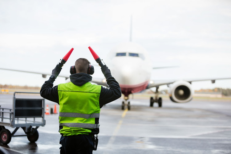 Ground crew signaling to airplane on runway.