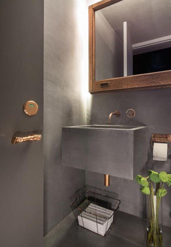 Torneira bronze de parede em lavabo, paredes e piso pretos e detalhes bronze.