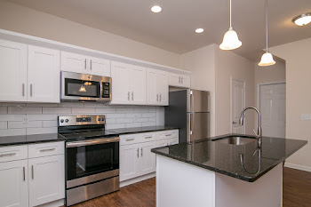 Fully-equipped kitchen with white cabinets and stainless steel appliances