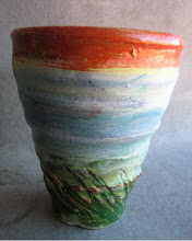 Photo: cup with pigmented slip on red clay with a clear glaze. The green is an underglaze, not a slip. Clay slip painted on the raw pot is very common with red earth clay.