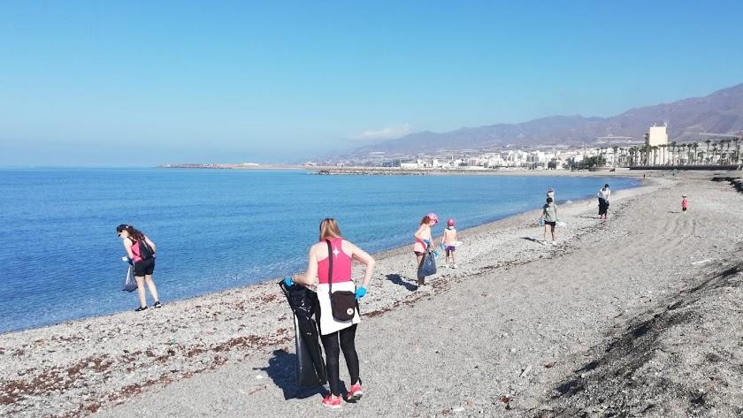 Voluntarios recogiendo residuos en la playa.