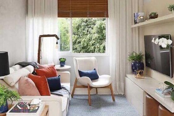 Sala com sofá e poltrona branca, almofadas e enfeites coloridos, painel branco com TV.