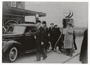 Photo: 1937 Het prinselijk paar, Juliana en Bernhard, tijdens hun huwelijksreis aan de Heuvelstraat 167 met hun donkergroene Ford. Zij vertrokken per auto via Breda naar Brussel en van daaruit per vliegtuig naar Polen (Krynica), per auto naar Mittersill, Zell am See (waar de koningin-moeder hen bezocht), Innsbruck, Rome, Monte Carlo en Parijs. Tijdens hun terugtocht tankte Bernhard onverwacht zijn auto bij de familie C.F. Naalden-van Hooydonk, die een winkel en Essotankstation had. Het prinselijk paar passeerde de grens te Wuustwezel en reed via Rijsbergen, Princenhage, Belcrum richting Moerdijk, naar Soestdijk. De auto was een groene Ford. De inwonenden van Princenhage vonden het een hele eer. Prins Bernhard zit achter het stuur, rechts van hem rechercheurs, achter de auto links C.F. Naalden en rechts mevrouw Naalden. Let op de omgeving: geheel onbebouwd!