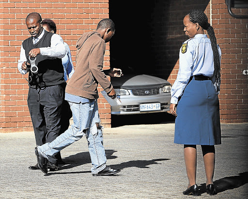 An accused in the gang-rape of a 17-year-old girl, outside the Roodepoort Magistrate's Court.