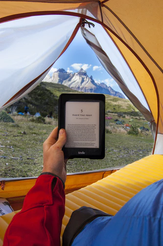 Reading an ebook in a tent with a mountain range in the background. The photo was taken by Frank Holleman at unsplash.com
