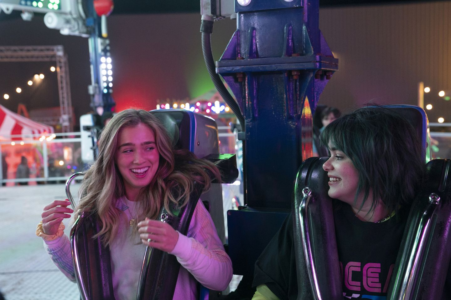 17 year old friends, Veronica (left) and Bailey (right) are at sitting side by side on a fairground ride that spins around. They are looking at each other and laughing, illuminated by bright coloured lights in the background.