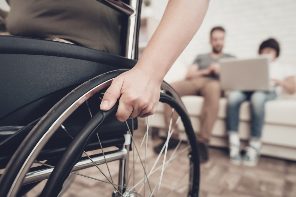 Someone in a wheelchair wheels away from from 2 people using a laptop