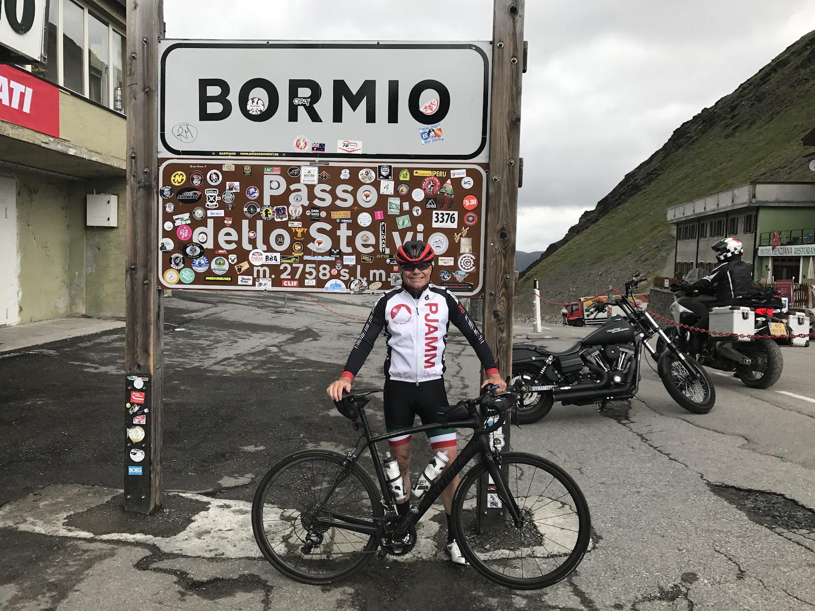 Bike climb Passo dello Stelvio - John Johnson PJAMM Cycling at pass sign with bicycle