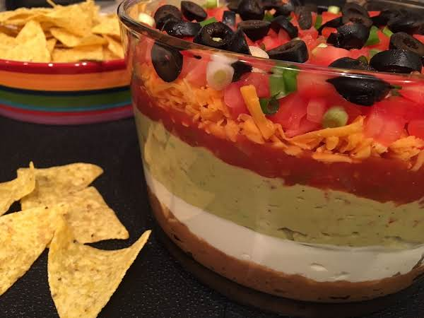 A Large Glass Bowl With Layers Of Food, Topped With Black Olives Sitting On A Black Table Mat With A Bowl Of Tortilla Chips.