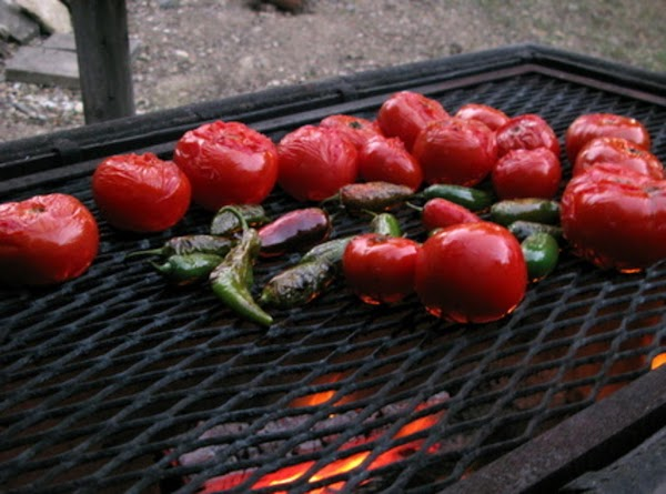 Place Jalapeños and tomatoes on a grill and grill until a little chard on...
