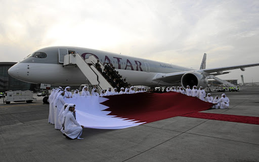 Flagging numbers: Qatar Airways staff hold a Qatari flag in front of an Airbus A350-1000 at Hamad. Picture4: REUTERS