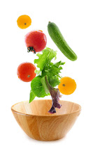 Photo: Assorted fresh vegetables falling into a wooden salad bowl isolated on white background
