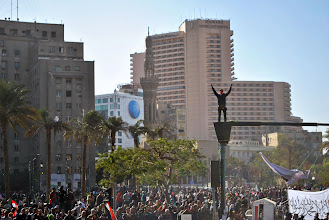 Photo: A man raises his arms from atop a light post in Tahrir Square.