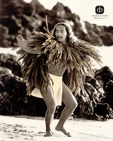 Photo: Hālo'alo'a - Resounding This Hawaiian man recites a genealogical chant while performing a traditional hula dance. His cape, made from dried Tī leaves, will help protect him from the harsh sun.