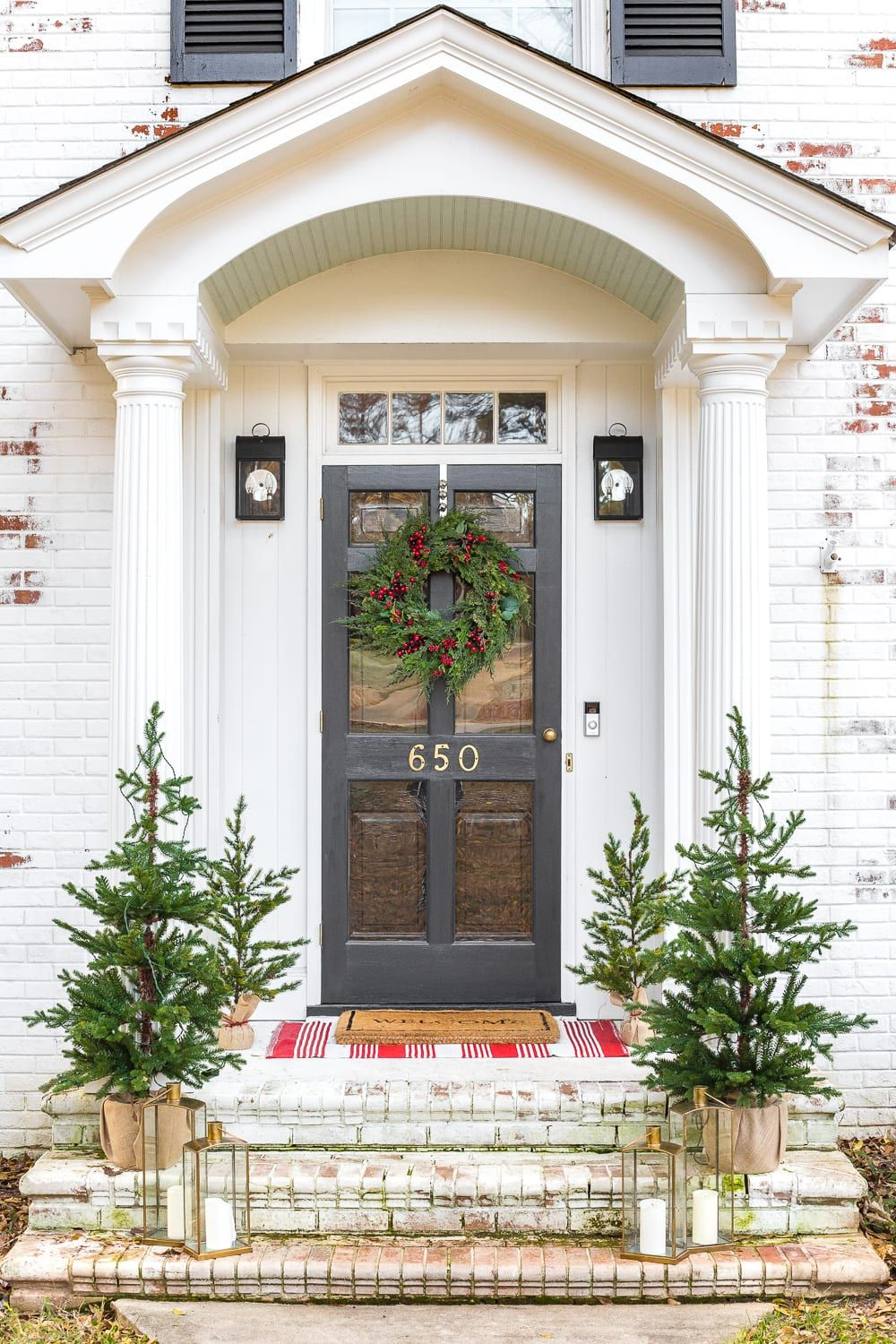 White house front door decorated for the holidays with a wreath and 4 small christmas trees and candles.