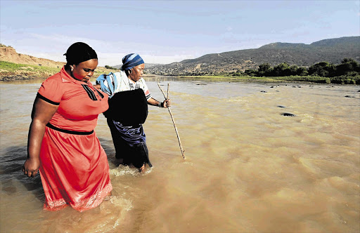 Zenzi Mchunu and Khethiwe Kubheka must wade across the uThukela River to collect their monthly government grants. When the river is swollen it becomes almost impossible for the elderly to cross. It has claimed many victims, they say Picture: TEBOGO LETSIE