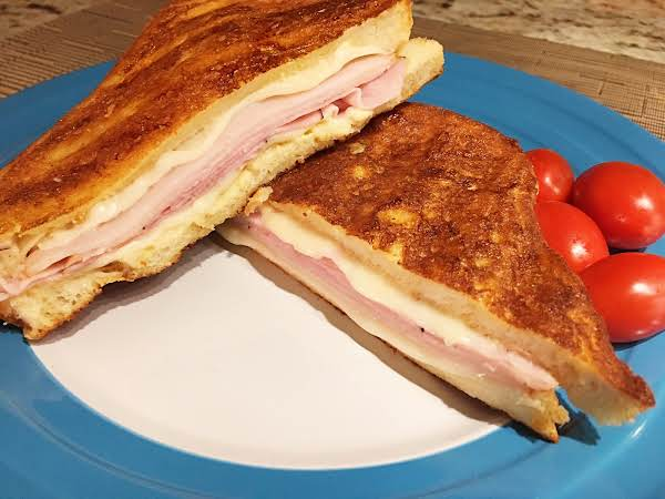 A Sandwich On A Blue Plate With Cherry Tomatoes.