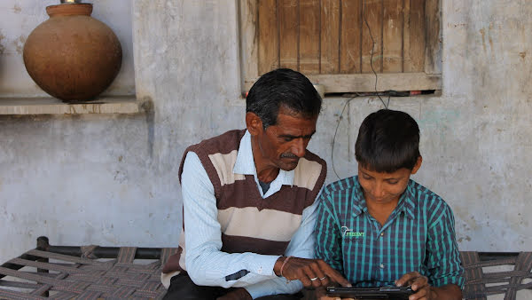 Man and a boy look at a tablet