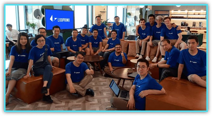 Group of people in blue Loopring tee shirts gathered in front of a monitor displaying Loopring logo.