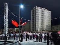 mensenmenigte bij nacht op straat met gebouw van 11 verdiepingen aan overkant