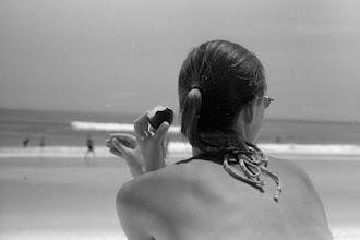 Photo: K. at the beach, eating a plum