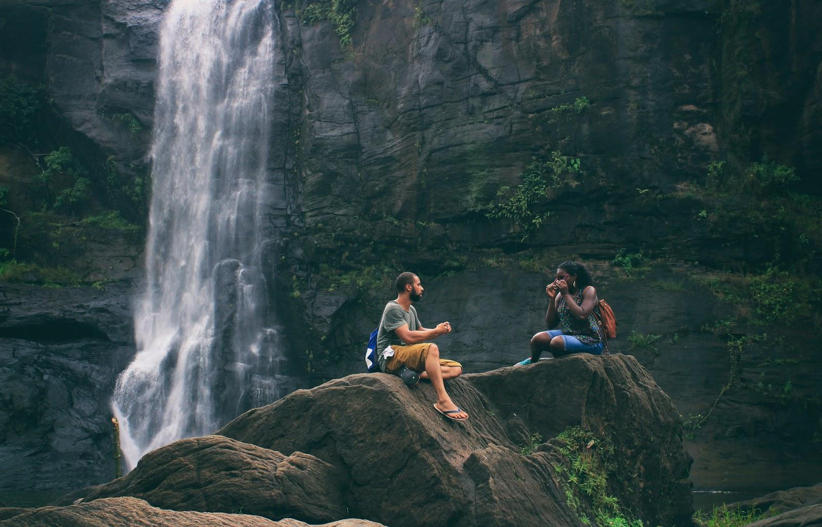 a girl and a boy talking by a waterfall