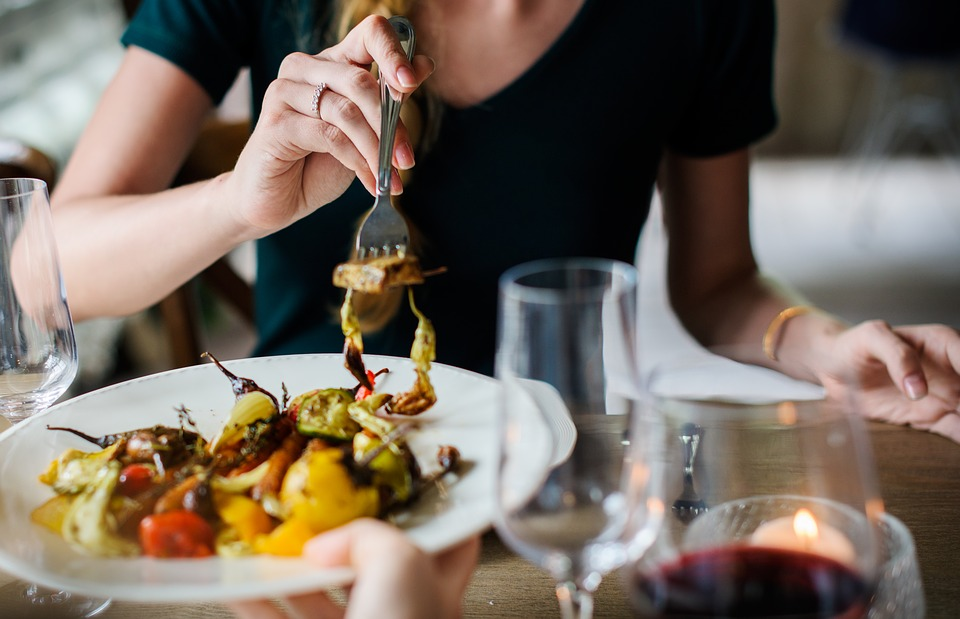 Mulher com talheres comendo comida saudável para alimentação equilibrada.
