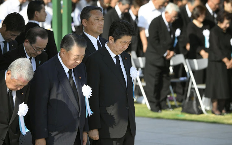 Japan's Prime Minister Shinzo Abe and other officials offer a silent prayers for the victims of the 1945 atomic bombing, at Peace Memorial Park in Hiroshima, western Japan on August 6 2018, on the 73rd anniversary of the atomic bombing of the city. Picture: KYODO/REUTERS