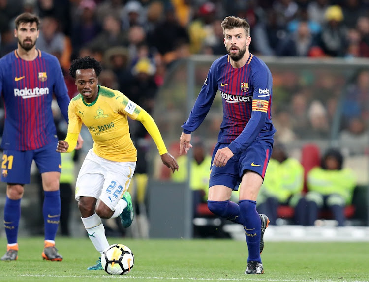 Gerald Pique of Barcelona challenged by Percy Tau of Mamelodi Sundowns during the 2018 Mandela Centenary Cup Friendly match between Mamelodi Sundowns and Barcelona at FNB Stadium, Johannesburg on 16 May 2018.