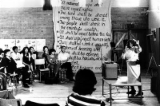 PEOPLE'S WISHES: Delegates discuss the clauses of the Freedom Charter in Kliptown in 1955. Pic. Unknown